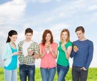 Glimlachende studenten met smartphones Stock Afbeeldingen