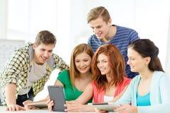 Glimlachende studenten met tabletpc op school Stock Fotografie