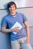 Glimlachende studentenjongen die tegen moderne muur leunen Stock Foto's