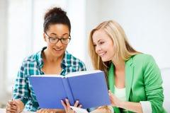 Glimlachende studentenmeisjes die boek lezen op school Stock Foto