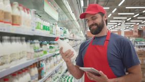 Glimlachende supermarktwerknemer die de kwaliteit van de melk controleren stock video