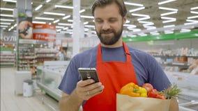 Glimlachende supermarktwerknemer die mobiele telefoon en het houden van het winkelen zak in supermarkt gebruiken stock video