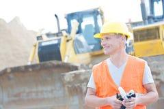 Glimlachende supervisor die weg bouwwerf bekijken Stock Afbeelding