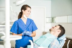 Glimlachende Tandarts In Scrubs Talking aan Patiënt bij Kliniek royalty-vrije stock afbeeldingen