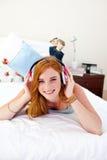 Glimlachende tiener die aan de muziek luistert stock fotografie