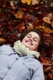 Glimlachende tiener die in de herfstbladeren ligt Stock Afbeeldingen