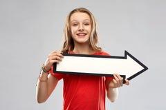 Glimlachende tiener met pijl die richting tonen stock foto