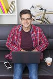Glimlachende tiener op laag met laptop stock foto's