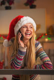 Glimlachende tiener in santahoed die mobiele telefoon in keuken spreken Stock Afbeelding