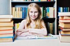 Glimlachende tiener tussen stapel van boek Royalty-vrije Stock Afbeelding