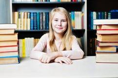 Glimlachende tiener tussen stapel van boek Royalty-vrije Stock Foto