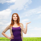 Glimlachende tienerholding iets op haar palm Stock Foto