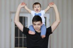 Glimlachende tienerjongen die zijn kleine broerzitting op zijn hals houden stock foto
