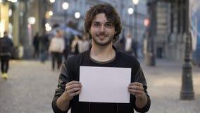 Glimlachende tienermens die een lege exemplaar ruimtebanner op de straat in de stad houden stock footage