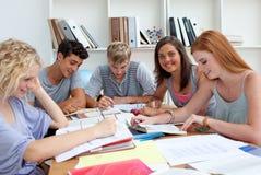 Glimlachende tieners die in de bibliotheek bestuderen stock foto