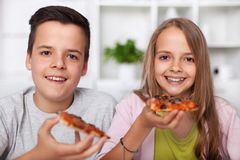 Glimlachende tieners, een jongen en een meisje, die een pizzaplak hebben - smil stock afbeelding