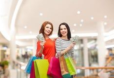 Glimlachende tieners met het winkelen zakken en geld Stock Fotografie