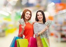 Glimlachende tieners met het winkelen zakken en geld Royalty-vrije Stock Afbeeldingen