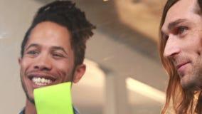 Glimlachende toevallige bedrijfsarbeiders die op kleverige nota's schrijven stock videobeelden