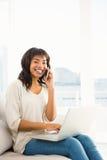 Glimlachende toevallige vrouw die een telefoongesprek hebben terwijl het gebruiken van laptop Stock Afbeeldingen