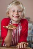 Glimlachende trotse jongen die de peperkoekmens steunen royalty-vrije stock afbeelding
