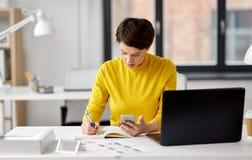 Glimlachende ui ontwerper die smartphone gebruiken op kantoor stock foto's