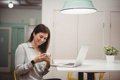 Glimlachende uitvoerende gebruikende mobiele telefoon Stock Afbeelding