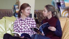 Glimlachende universitaire meisjes die in bibliotheek babbelen stock footage