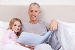 Glimlachende vader die een verhaal lezen aan zijn dochter stock afbeelding