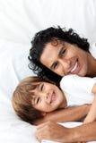 Glimlachende vader die zijn kleine jongen koestert Stock Afbeeldingen