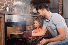 Glimlachende vader en dochter die cake van oven nemen stock fotografie