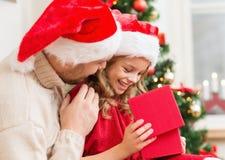 Glimlachende vader en dochter het openen giftdoos stock foto's