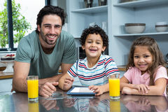 Glimlachende vader en kinderen die tablet gebruiken Stock Fotografie