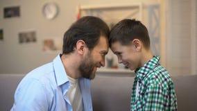 Glimlachende vader en weinig zoon wat betreft voorhoofden, vertrouwende relaties, vrienden stock footage
