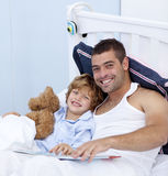Glimlachende vader en zoon die een boek in bed lezen Royalty-vrije Stock Afbeelding