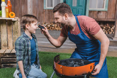 Glimlachende vader en zoon die grill voor barbecue voorbereiden stock foto's