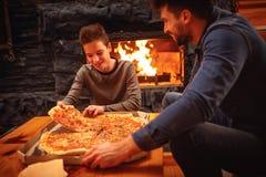 Glimlachende vader en zoon die pizza samen eten Stock Afbeelding