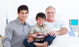 Glimlachende vader en zoons bezoekende grootvader Royalty-vrije Stock Foto