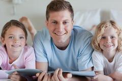 Glimlachende vader met zijn kinderen en een tijdschrift Stock Fotografie