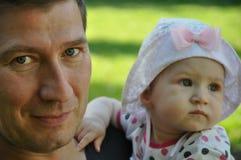 Glimlachende vader met zijn portretten van de babydochter in openlucht op de groene vage achtergrond stock afbeeldingen