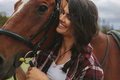 Glimlachende veedrijfster met haar paard stock foto's