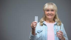 Glimlachende verouderde dame die de kwaliteit van het pillenmedicijn, immuniteit tonen die drugs versterken stock videobeelden