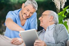 Glimlachende Verpleegster Assisting Senior Man die in Tablet gebruiken