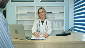 Glimlachende verpleegster die met laptop benoeming plannen voor mannelijke patiënt bij ontvangst Royalty-vrije Stock Foto's