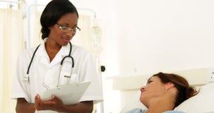 Glimlachende verpleegster die op haar patiënt controleren stock footage