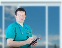 Glimlachende verpleger die nota's neemt stock foto's