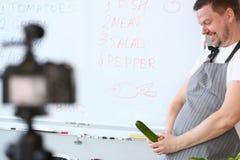Glimlachende Vlogger-Chef-kok Recording Cucumber Joke royalty-vrije stock afbeeldingen