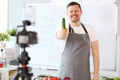 Glimlachende Vlogger-Chef-kok Recording Green Cucumber stock foto