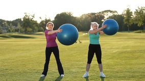 Glimlachende volwassen vrouwen die ab-oefeningen met ballen doen stock video