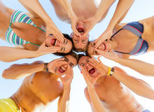 Glimlachende vrienden in cirkel op de zomerstrand Royalty-vrije Stock Afbeeldingen